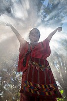 Woman standing in smoke in forest.