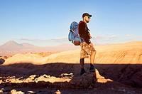 Atacama, Chile-september 14, 2014: A mature caucasian hiker with his backpack on the peak of montain watching the sunset on Atacama desert in Chile.