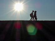 People walking on a dyke on island Neuwerk, Elbe estuary, North Sea, Hamburg, Germany.