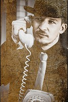 Tatty and worn image of a retro secret intelligence operative in black suit talking on the rotary telephone. A call of interception.