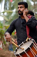 India, Kerala, Kannur surroundings, Procession marking the opening of a Theyyam festival, Drummer chatting with his cell phone.