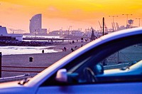 Beach at sunset. First, detail of a blurred car. In the background, beach and Hotel W by Ricardo Bofill architect. Hotel W, aka Vela Hotel, highlighti...