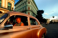Old car 1950s Chevrolet passing the Saratoga Hotel, Paseo de Marti, Old Havana, Cuba.