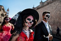 A young couple, costumed as â. . La Catrinaâ. . , a Mexican pop culture icon representing the Death, walks through the town during the Day of the Dead...