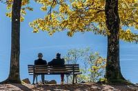 Couple enjoying the last rays of sunshine in the autumn on a bench at a lake, Kochel, Bavaria, Upper Bavaria, Deuschland, Europe.
