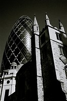 The Gherkin, or 30 St Mary Axe, and St Andrew Undershaft in the City of London in England in the United Kingdom.