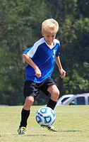 Young boy playing soccer wearing blue jersey.