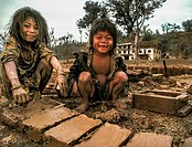 Brother and sister make mud bricks in wooden frame for parents house, Arun valley, Nepal.