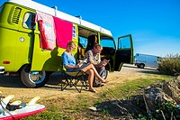 man and young woman sit and read next to camper with surfboards with view at the coast of Portugal