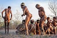 Kalahari San people dancing in circles around people sitting down on the ground and singing.