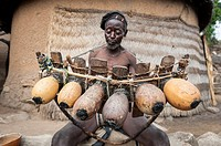 Old man from the Koma tribe playing the marimba, an intrument made out of wood and calabashes.