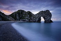 Colorful sky at dawn over Durdle Door along the Jurassic Coast, Dorset, England.