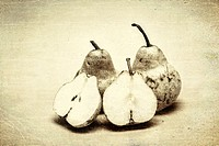 Close-up vintage still of three ripe pears. One of them halved.