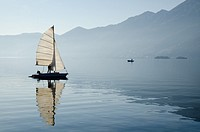 Sailing boat reflected on alpine lake Maggiore with Brissago islands and mountain in Ascona, Switzerland.