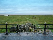 Steps down to the grass and rocks from the promenade in Grange-Over-Sands looking towards Morecambe Bay, Cumbria, UK