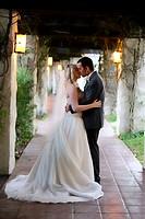 bride & groom embracing & kissing after wedding