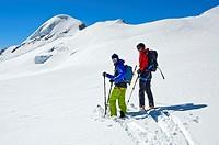 Two skiers on a ski tour on the Aebeni Flue firn fiel beneath the Mittagshorn peak, Loetschental, Valais, Switzerland.