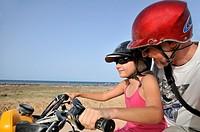 Girl (10) driving an ATV with her dad by seacoast, Djerba Island, Tunisia.