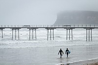 Surfers near Saltburn`s Victorian pier as sea fog roll in of the North sea at Saltburn by the Sea, North Yorkshire, England, United Kingdom.