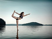 Young woman practicing Hatha yoga on a floating platform in water on the lake during sunrise in the morning. Yoga Dancer posture, Dandayamana Dhanuras...