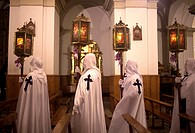 Hooded penitents wearing the cross of Saint James hold candles during an Easter Holy Week procession in Astorga, Castilla y Leon, Spain.
