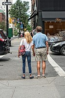 Older Caucasian Man, 50s - 60´s, Romantically Holding Hands with a Younger Caucasian Woman, 40´s - 50´s. Waiting at a stop light to cross a street, Ma...