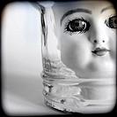 Primer plano de una cabeza de muñeca de porcelana mirando fijamente a la camara desde el interior de un bote de cristal. Close up of a porcelain doll ...