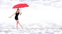 Barefoot woman, walking very focused on a rope with a red umbrella in hand, on the bottom white clouds in a blue sky.