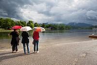 Rear view of three women sheltering under a umbrella. Staffelsee. Upper Bavaria. Germany.