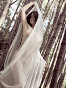 Beautiful artistic nude portrait of a young woman covered with white shawl in a pine forest nature scenery in bright sunlight.
