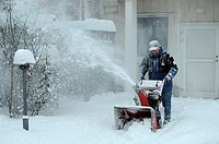 Man with snowblower clearing snow.
