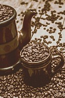Nostalgic cafe scene of a rustic brown cup and teapot overflowing with roasted coffee beans. Coffee shop decor.