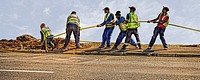 A team of men working. Pulling through fibre optic cable connection. Cape Town, South Africa.