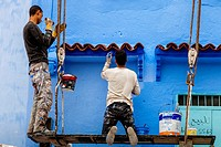 Local Men Paint The Outside Of A House In Traditional Blue, The Medina, Chefchaouen, Morocco.