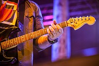 man playing electric guitar on stage