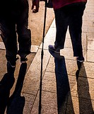 shadow of walking mens, one with a stock.