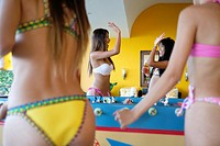 Young woman high five each other after scoring at table football game.