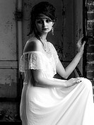 A 25 year old woman wearing a white dress looking away from the camera standing in an abandoned building, black and white.