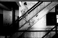 Side view of a nude 25 year old woman descending a stairway, holding an old parasol in an abandoned building, black and white.