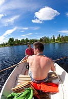 Brothers rowing a boat, countryside of northern Sweden.