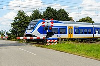 HOEVEN, THE NETHERLANDS - AUGUST 1: Train moving at high speed on a level crossing on August 1, 2016 in The Netherlands.