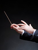 Hands of Conductor with Baton Leading Orchestra.