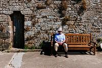 Elder man sitting on bench at l´Anse des sablons beach promenade, Saint Malo, Ille-et-Vilaine, Brittany, France.