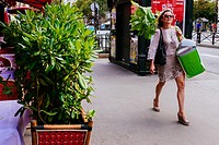 Young woman walking down street carrying a big plant and passing by plants in pots, Paris, Île-de-France, France.