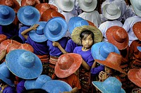 A girl looking to the camera among the many children with colourful hats in a celebration.