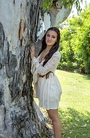 Eighteen year old girl standing near a tree, La Jolla, California.