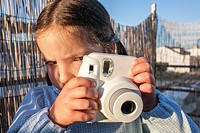 Cute little happy girl with instant picture photo camera. Outdoor.