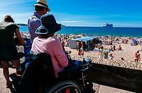 Woman on wheelchair looking over the beach. Saint-Jean-de-Luz, Basque Country, France.