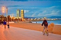 People near Barceloneta beach at dusk. At the bottom, Hotel Arts building and Mapfre tower building. Barceloneta quarter, Barcelona, Catalonia, Spain