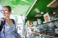 Merida, Spain - May 14, 2017: Young atractive woman ordering meal at green food truck, in the historical city of Merida, Extremadura, Spain.